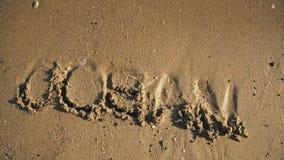 Λέξη ` ωκεάνιο ` στην άμμο που πλένεται από την άποψη κυμάτων φιλμ μικρού μήκους