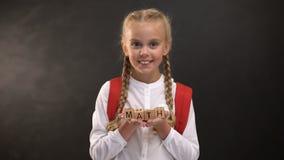 Λέξη Math στους ξύλινους κύβους στα χαριτωμένα χέρια μαθητριών, εκπαιδευτικό σύστημα, μάθημα φιλμ μικρού μήκους