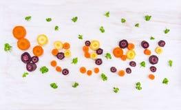 Λέξη veggy των ζωηρόχρωμων τεμαχισμένων καρότων †‹â€ ‹με τα φύλλα μαϊντανού Στοκ Εικόνες