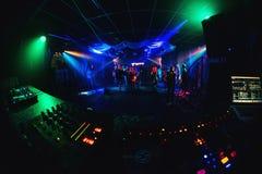 Λέσχη νύχτας με τους χορεύοντας ανθρώπους στη πίστα χορού, revelers σε ένα κόμμα και έναν πίνακα μουσικής του DJ Στοκ Εικόνες