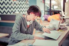 Λήξη σπουδαστών που λειτουργεί σε χαρτί σειράς μαθημάτων του στοκ εικόνα με δικαίωμα ελεύθερης χρήσης