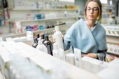 Λήψη ενός μπουκαλιού με τα καλλυντικά στο φαρμακείο te Στοκ φωτογραφία με δικαίωμα ελεύθερης χρήσης