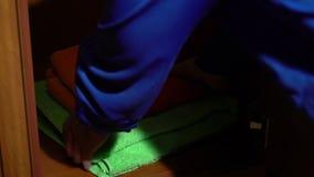 Λήψη ενός συνόλου πετσετών από μια ντουλάπα φιλμ μικρού μήκους