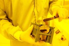 Λήψη μιας μεγάλης γκοφρέτας από έναν δίσκο με έναν κενό tweezer Στοκ Φωτογραφία