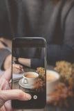 Λήψη μιας φωτογραφίας από το δάχτυλο που πιέζει σε Smartphone για τη φωτογραφία Γ Στοκ Φωτογραφία