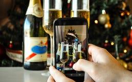 Λήψη μιας φωτογραφίας των γυαλιών χριστουγεννιάτικων δέντρων και σαμπάνιας με ένα smartphone Στοκ εικόνα με δικαίωμα ελεύθερης χρήσης