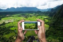 Λήψη της φωτογραφίας τοπίων φύσης με έξυπνο τηλέφωνο στην αιχμή βουνών, που ταξιδεύει στην τροπική χώρα Στοκ Φωτογραφίες