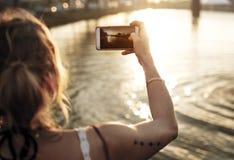 Λήψη της φωτογραφίας του ηλιοβασιλέματος από τη λίμνη Στοκ Φωτογραφίες