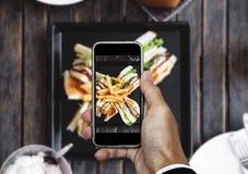 Λήψη της φωτογραφίας τροφίμων, φωτογραφία τροφίμων με έξυπνο τηλέφωνο, σάντουιτς λεσχών με τις τηγανιτές πατάτες στον ξύλινο πίνα Στοκ Φωτογραφία