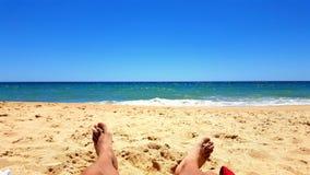 Λήψη του ήλιου στην παραλία άμμου κοντά στη θάλασσα στοκ εικόνες