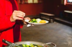 Λήψη των τροφίμων από τον μπουφέ Στοκ Φωτογραφίες