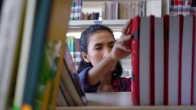 Λήψη φοιτητών πανεπιστημίου και διαβασμένο βιβλίο στη βιβλιοθήκη απόθεμα βίντεο