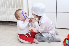 Λίγα 4 έτη αδελφών και 10 μήνες αδελφών παίζουν το γιατρό στο σπίτι Στοκ Φωτογραφίες