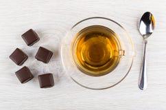 Λίγα μικρά μελοψώματα στη σοκολάτα, το κουταλάκι του γλυκού και το φλυτζάνι του τσαγιού Στοκ Φωτογραφία
