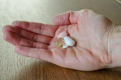 Λίγα χάπια στο χέρι της γυναίκας στο ξύλινο επιτραπέζιο υπόβαθρο στοκ εικόνες