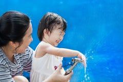 Λίγες ασιατικές κορίτσι και μητέρα παίζουν με τη μάνικα νερού Στοκ εικόνες με δικαίωμα ελεύθερης χρήσης