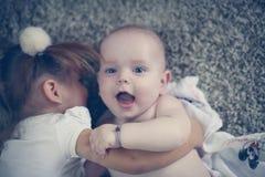 Λίγη αδελφή αγκαλιάζει έναν αδελφό μωρών Συγκίνηση αγάπης Στοκ φωτογραφία με δικαίωμα ελεύθερης χρήσης