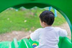 Λίγη ασιατική παίζοντας φωτογραφική διαφάνεια παιδιών στην παιδική χαρά κάτω από το sunli Στοκ Φωτογραφία