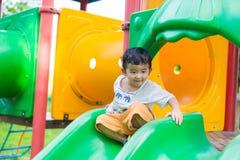 Λίγη ασιατική παίζοντας φωτογραφική διαφάνεια παιδιών στην παιδική χαρά κάτω από το sunli Στοκ Εικόνα