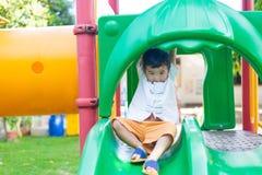 Λίγη ασιατική παίζοντας φωτογραφική διαφάνεια παιδιών στην παιδική χαρά κάτω από το sunli Στοκ φωτογραφίες με δικαίωμα ελεύθερης χρήσης