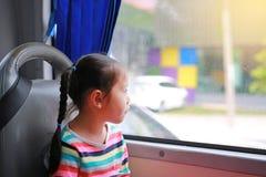 Λίγη ασιατική συνεδρίαση κοριτσιών στο λεωφορείο δημόσιων συγκοινωνιών και κοίταγμα έξω στοκ φωτογραφίες