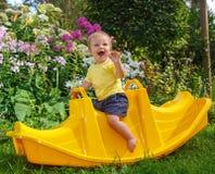 Λίγη αστεία συνεδρίαση αγοριών στην ταλάντευση μωρών Στοκ εικόνες με δικαίωμα ελεύθερης χρήσης