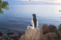 Λίγη γοργόνα κάθεται σε έναν απότομο βράχο στο ηλιοβασίλεμα Στοκ φωτογραφίες με δικαίωμα ελεύθερης χρήσης