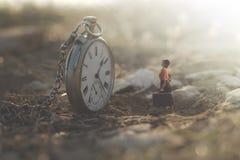 Λίγη γυναίκα εξετάζει κατάπληκτη το μεγάλο ρολόι στοκ εικόνες