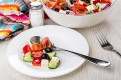Λίγη ελληνική σαλάτα και κουτάλι στο πιάτο, άλας, πετσέτα Στοκ Εικόνες