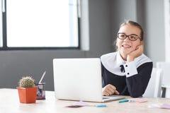 Λίγη επιχειρηματίας που εργάζεται στο lap-top στην αρχή στον εργασιακό χώρο στοκ εικόνες