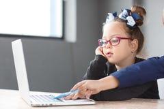 Λίγη επιχειρηματίας που εργάζεται στο lap-top στην αρχή στον εργασιακό χώρο Στοκ Φωτογραφίες