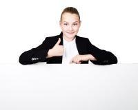 Λίγη επιχειρησιακή γυναίκα που στέκεται πίσω και που κλίνει σε έναν άσπρη κενή πίνακα διαφημίσεων ή μια αφίσσα, εκφράζει διαφορετ Στοκ εικόνα με δικαίωμα ελεύθερης χρήσης