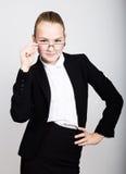 Λίγη επιχειρησιακή γυναίκα στα γυαλιά σκεπτόμενα μια νέα ιδέα Πορτρέτο στούντιο του κοριτσιού παιδιών στο επιχειρησιακό ύφος Στοκ Εικόνες