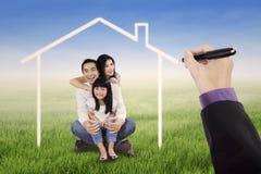 Λίγη ευτυχής οικογένεια με ένα σπίτι ονείρου Στοκ φωτογραφία με δικαίωμα ελεύθερης χρήσης
