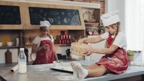 Λίγη κόρη έχει τη διασκέδαση προετοιμάζοντας μια ζύμη σε μια άνετη κουζίνα Αυτοί που προετοιμάζουν τα μπισκότα Χριστουγέννων Οικο απόθεμα βίντεο