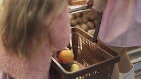 Λίγη κόρη και η μητέρα της κρατούν ένα καλάθι και διπλώνουν τα τρόφιμα απόθεμα βίντεο