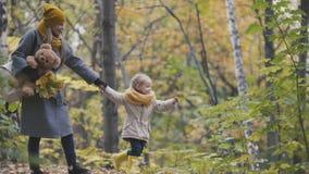 Λίγη κόρη με τη μαμά της και Taddy αντέχουν τους περιπάτους στο πάρκο φθινοπώρου - παιχνίδια τα φύλλα Στοκ Φωτογραφίες