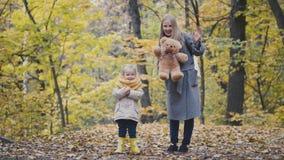 Λίγη κόρη με τη μητέρα της και Teddy αντέχουν στο πάρκο φθινοπώρου Στοκ φωτογραφία με δικαίωμα ελεύθερης χρήσης