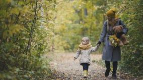 Λίγη κόρη με τη μητέρα της και Teddy αντέχουν στο πάρκο φθινοπώρου Στοκ εικόνες με δικαίωμα ελεύθερης χρήσης