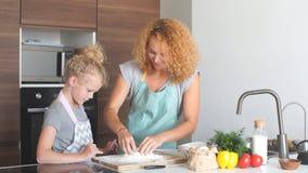 Λίγη κόρη που βοηθά το ψήσιμο μητέρων στην κουζίνα, την οικογένεια και το μαγείρεμα απόθεμα βίντεο