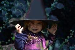 Λίγη μάγισσα, κορίτσι Α σε ένα κοστούμι μαγισσών, κορίτσι έντυσε ως μάγισσα στο δάσος με το καπέλο, αποκριές στοκ εικόνες