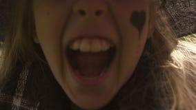 Λίγη μάγισσα που κάνει το τρομακτικό πρόσωπο στη κάμερα που έχει τη διασκέδαση στην ευτυχία κομμάτων αποκριών απόθεμα βίντεο