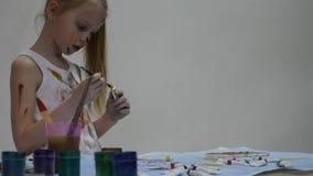 Λίγη μαθήτρια Ο χαριτωμένος ζωγράφος μικρών κοριτσιών επισύρει την προσοχή στον πίνακα και σε τον στα ενδύματά της o απόθεμα βίντεο