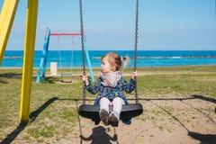 Λίγη μύγα κοριτσάκι με τη διασκέδαση στην ταλάντευση σχοινιών στην παραλία θάλασσας με τα κύματα και την κυματωγή στο τροπικό νησ Στοκ Εικόνες