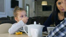Λίγη ξανθή συνεδρίαση τσαγιού κατανάλωσης κοριτσιών στον καφέ με τους καλούς γονείς της στοκ φωτογραφία με δικαίωμα ελεύθερης χρήσης