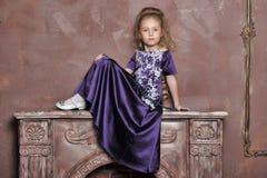 Λίγη πριγκήπισσα ξανθή στο ιώδες φόρεμα Στοκ Φωτογραφία