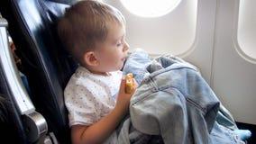 Λίγη συνεδρίαση αγοριών μικρών παιδιών δίπλα στο φωτιστικό στο αεροπλάνο και την κατοχή ενός πρόχειρου φαγητού στοκ φωτογραφίες με δικαίωμα ελεύθερης χρήσης