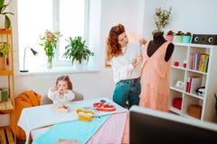 Λίγη συνεδρίαση κορών που κάνει πλησίον mom τη μέτρηση το κοντινό φόρεμα από στοκ φωτογραφία με δικαίωμα ελεύθερης χρήσης