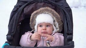 Λίγη συνεδρίαση χαμόγελου κοριτσάκι στον περιπατητή ελκήθρων στη χειμερινή εξάρτηση 4k ημέρας χειμερινού χιονιού απόθεμα βίντεο