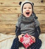 Λίγη συνεδρίαση κοριτσιών χαμόγελου με το δώρο Στοκ φωτογραφία με δικαίωμα ελεύθερης χρήσης